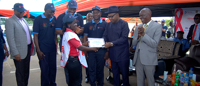 Hon. Festus Ovie Agas the SSG Delta State Presenting a Certificate to one of the Trained Peer Educators
