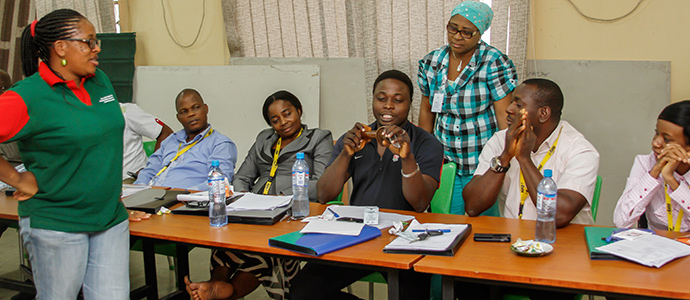 Participants demonstarting the use of a condom at a training